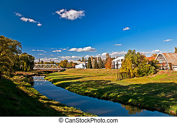 Factory on the river. Landscape - The river flows near to...