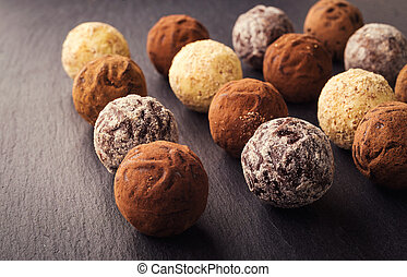 Chocolate truffle,Truffle chocolate candies with cocoa powder.Chocolate candies collection.Assorted chocolate truffles with cocoa powder, coconut and chopped hazelnuts on a dessert plate.