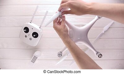 man make ready a drone for a flight, on a white table - man...