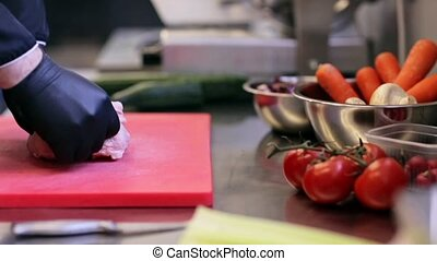 hands of chef chopping poultry meat in kitchen - cooking,...
