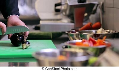 hands of male chef chopping eggplant in kitchen - cooking,...