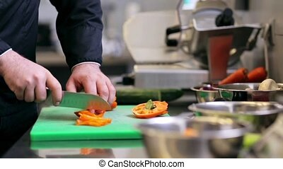 hands of male chef chopping paprika in kitchen - cooking,...