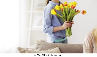 happy girl giving flowers to mother at home - people,...