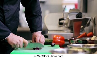 hands of male chef cook chopping onion in kitchen - cooking,...