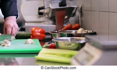 hands of male chef chopping champignons in kitchen -...
