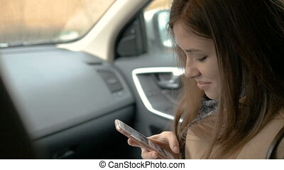 Young beautiful girl writes sms, sitting in the car in the...