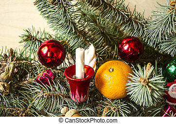 Pine branch with a candle, tangerine and Christmas toys on...
