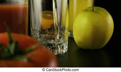 Apple juice is poured into one of the three glasses on the table. Slow mo