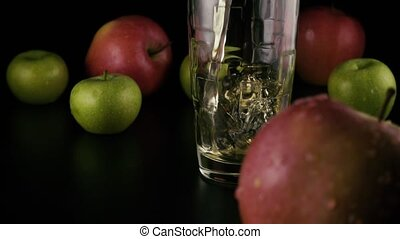 Apple juice is poured into a faceted glass. Slow motion.