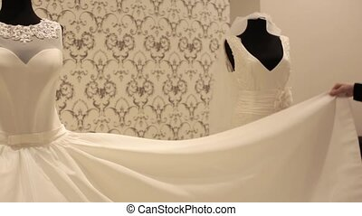 close-up of dummy with wedding dress, young beautiful woman choosing a white gown in a wedding shop.