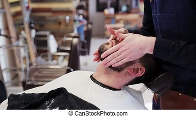 barber applying beard styler to male face - beauty,...