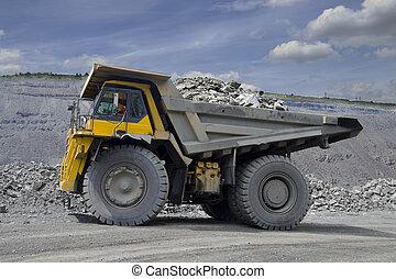 Heavy mining truck - Heavy mining dump truck driving along...
