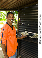 native Corn Island Nicaragua man bowl of rundown rondon food specialty freshly cooked outdoors zinc roof shack home