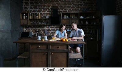Romantic couple sharing croissant in kitchen - Attractive...