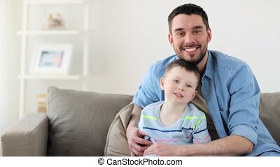 happy father and little son hugging at home - family,...