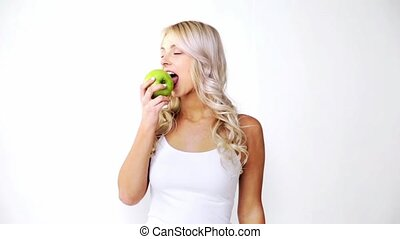 happy beautiful young woman eating green apple - healthy...