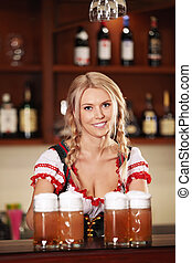 Young girl with beer - Attractive girl in a bar with beer
