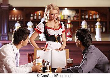 Menu - Attractive waitress shows visitors the menu bar