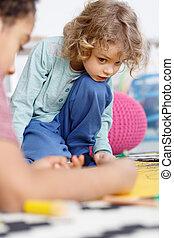 Boy painting in kindergarten