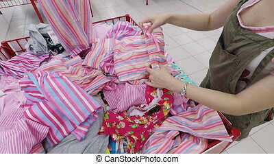 Young woman looking for cheap clothes in a store - Caucasian...