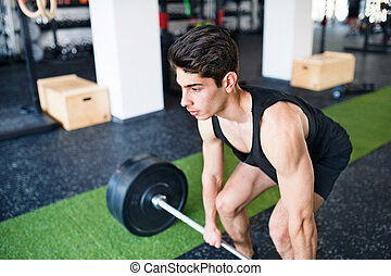 Young fit hispanic man in gym lifting heavy barbell, flexing...