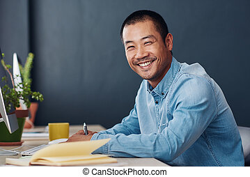 Smiling young Asian entrepreneur working at his office desk