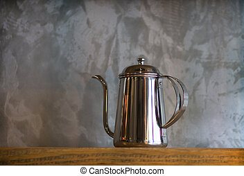 Silver coffee pots on wood shelf for home interior.