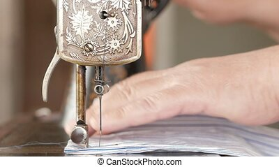 Men's hands sew on an old hand sewing machine.