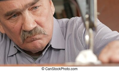 An adult man with a mustache sews on an old hand-sewn...