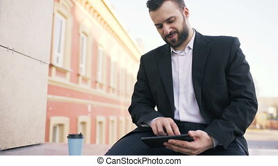 Young bearded businessman reading news on tablet computer during break in city street