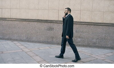 Dolly shot of young bearded business man talking at...