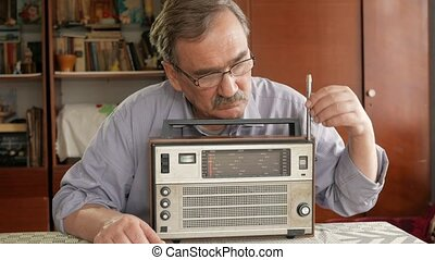An elderly man with a mustache turn on a vintage radio and...