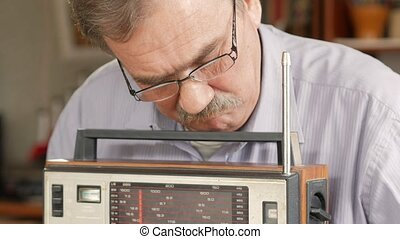 An elderly man with a mustache turn on a vintage radio and listens to music. Pulls out the antenna, turns on the button