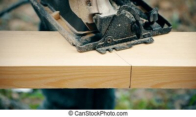 Cutting a wooden plank with portable circular saw