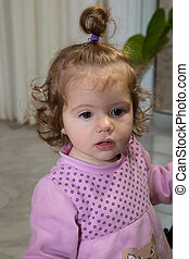 Charming little brown-eyed girl in a pink dress with a bow