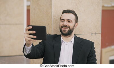 Young businessman talking on tablet computer having video chat with his wife. Business man using app to have video conference conversation with his family during break