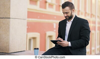 Young bearded businessman reading news on tablet computer...