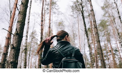 The back of a girl with long hair. She walks alone. Bright girl in the forest. Contrast with nature.