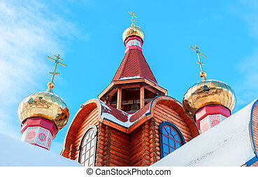 Domes with crosses on wooden orthodox church against the blue sky in Samara, Russia