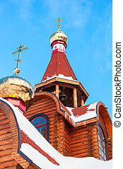 Domes with crosses on wooden orthodox church against the...