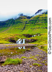Cloudy day in Iceland. Mountains and waterfalls. Cascade...