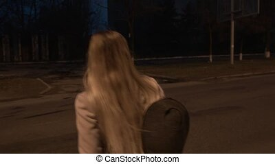 Young businesswoman crosses the road at night. The camera...