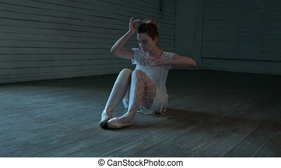 A young girl in bright clothes is sitting on the floor and creating dance movements with her hands. Sexy woman is sitting on the floor in a short dress. Dance with the hands.