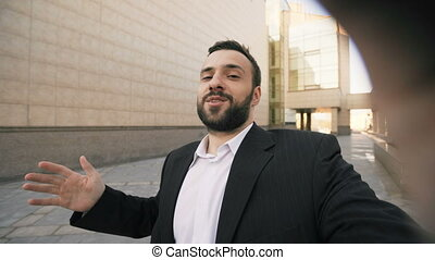 Young bearded business man talking smartphone having video...