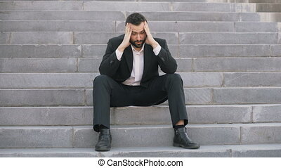 Upset young business man having stress and sitting on stairs in street. Businessman having deal problems concept