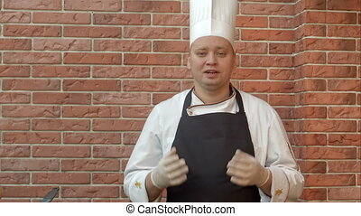 Smiling cook standing in the kitchennd talking to the camera...