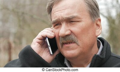 An elderly man with a mustache smokes and talks on the phone...