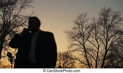 Blurred silhouette of business man in coat talking at smartphone and making deals on street with sunlight backlit in evening time