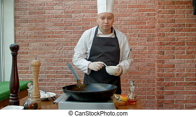 Handsome chef preparing pan with batter and talking to...