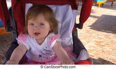 Baby girl sitting in carriage and smiling to camera